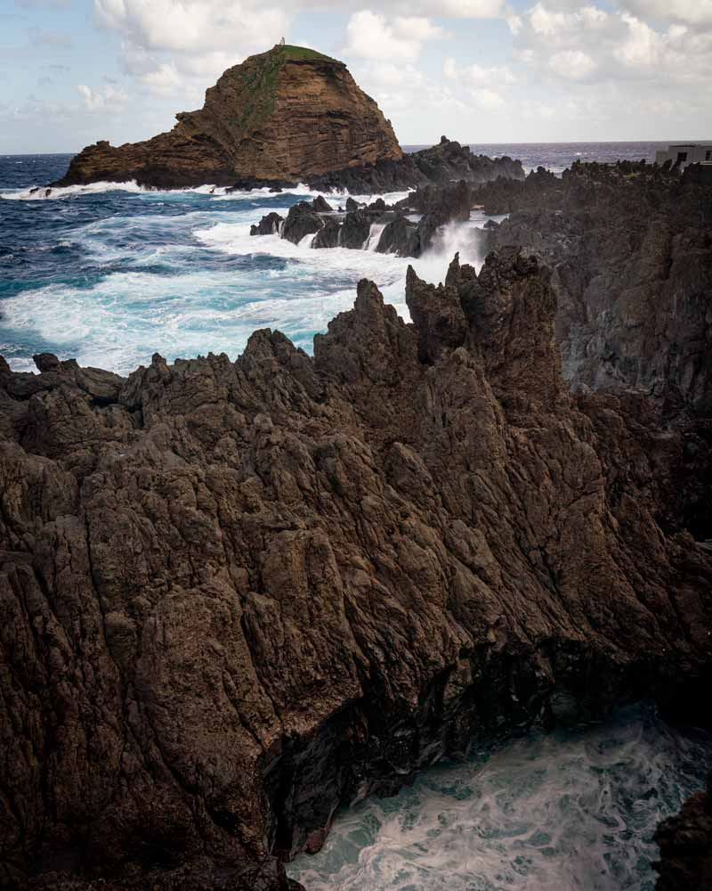 Dramatic rock formations around Porto Moniz with waves crashing against them and sending spray flying